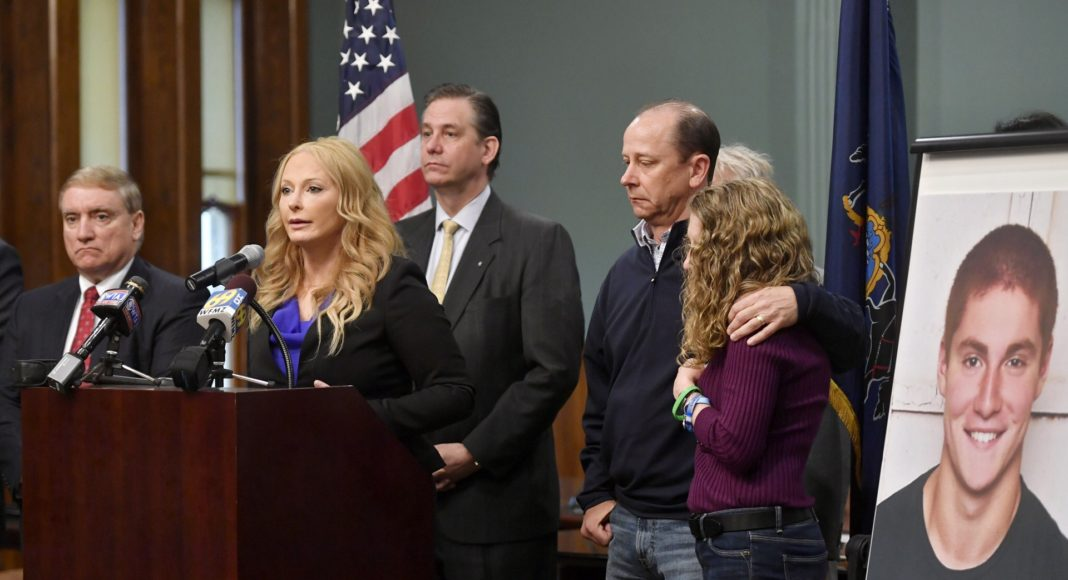 Jim and Evelyn Piazza stand by as Centre County District Attorney Stacy Parks Miller, left, announces the results of an investigation into the death of their son Timothy Piazza, seen in photo at right, a Penn State University fraternity pledge, during a press conference Friday, May 5, 2017, in Bellefonte, Pa. Timothy Piazza had toxic levels of alcohol in his body and was badly injured in a series of falls, authorities said Friday in announcing criminal charges against members of the organization and the frat itself. (Abby Drey/Centre Daily Times via AP)