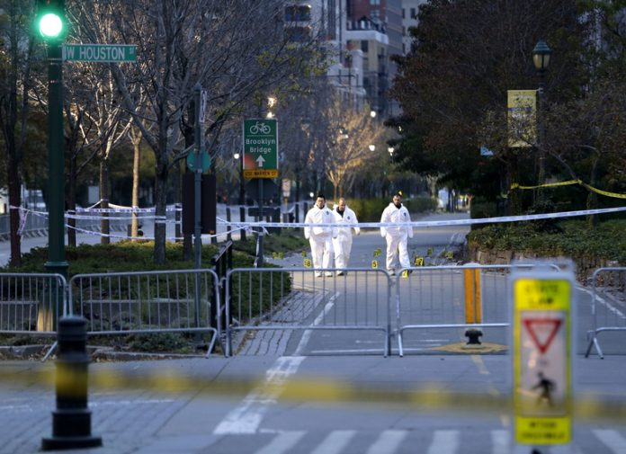 Emergency officials walk near evidence markers on the west side bike path in lower Manhattan, New York, Wednesday, Nov. 1, 2017. Investigators worked through the night to determine what led a truck driver to plow down people... (AP Photo/Seth Wenig)