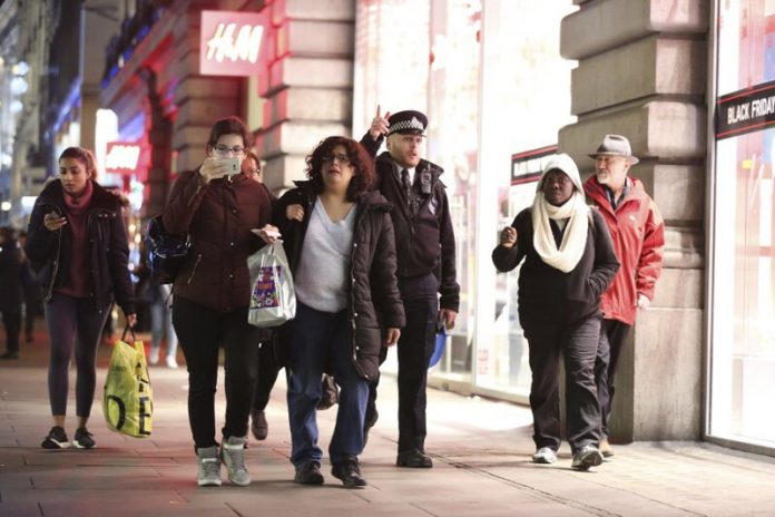 People are ushered by a police officer down a street in the west end of London after Oxford Circus station was evacuated Friday Nov. 24, 2017. British police said Friday they were responding to reports of an incident at Oxford Circus subway station, one of London's busiest. (Isabel Infantes/PA via AP)
