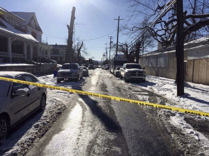 Crime tape stretches across a road near the scene of a shooting Thursday, Jan. 18, 2018, in Harrisburg, Pa. The mayor of Harrisburg said a U.S. marshal is dead after being shot while serving an arrest warrant in the city. Mayor Eric Papenfuse said two other officers were wounded in the Thursday morning shooting. (AP Photo/Marc Levy)