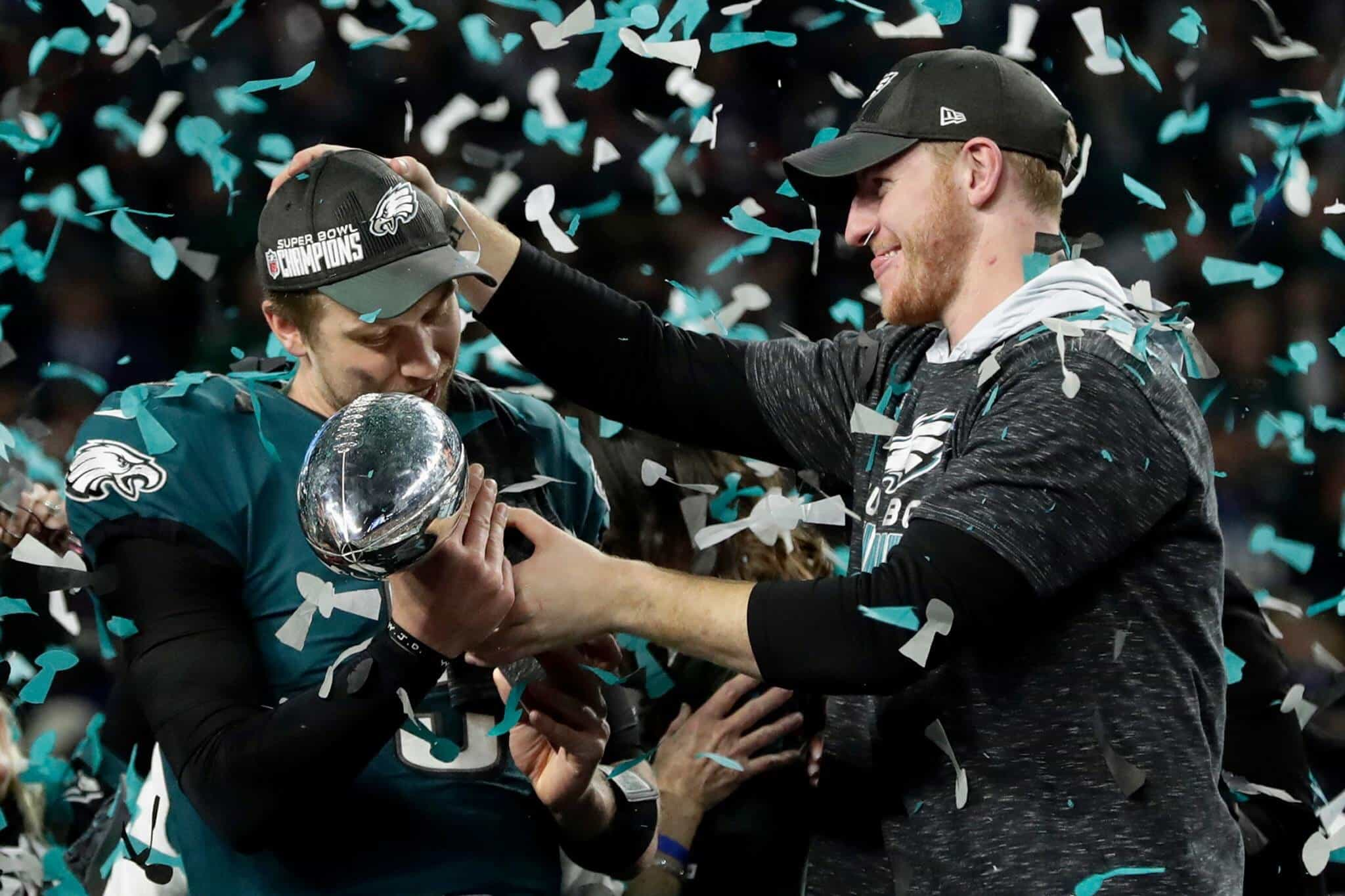 FILE - In this Sunday, Feb. 4, 2018, file photo, Philadelphia Eagles quarterback Carson Wentz, right, hands the Vincent Lombardi trophy to Nick Foles after winning the NFL Super Bowl 52 football game against the New England Patriots in Minneapolis. The Eagles aren't just celebrating their first championship since 1960 but also an abundance of talent at the position in franchise QB Carson Wentz and Super Bowl MVP Nick Foles. Should Wentz's recovery go well, the Eagles will have a huge bargaining chip to restock their roster. (AP Photo/Frank Franklin II, FIle)