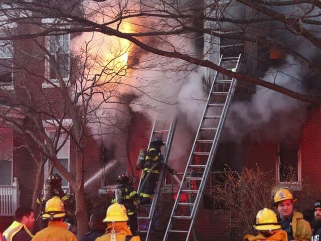 Firefighters work at a house fire in the 400 block of W. 23rd Street in Wilmington, reported before 7:30 pm Sunday. (WILLIAM BRETZGER, THE NEWS JOURNAL)