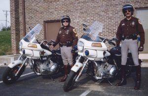 Doug Poppa (r) with Sgt. George Diehl in police attire prior to being fired for illegally using his position to place his wife under surveillance.
